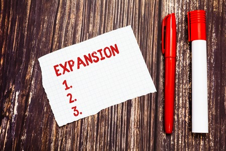 Photo for Handwriting text Expansion. Concept meaning action becoming larger or more extensive enlargement of something Blank Torn Index sized Graph Paper Two Pens for Writing on Wood Surface - Royalty Free Image