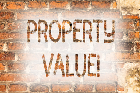 Writing note showing Property Value. Business photo showcasing Estimate of Worth Real Estate Residential Valuation Brick Wall art like Graffiti motivational call written on the wall
