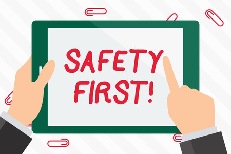 Photo pour Text sign showing Safety First. Business photo showcasing best avoid any unnecessary risks and act so that you stay safe Hand Holding Pointing Touching Blank Rectangular Color Tablet White Screen - image libre de droit