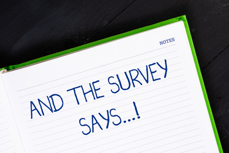 Text sign showing And The Survey Says. Business photo showcasing written spoken results of short quiz or exam on internet Close up view corner blank page notebook. Writing ideas projects goals