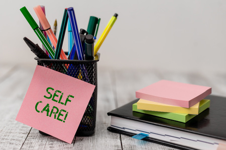 Foto de Handwriting text Self Care. Conceptual photo practice of taking action to preserve or improve ones own health Writing equipment and note paper sheets with agenda book on the wooden desk - Imagen libre de derechos