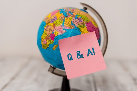 Word writing text Q And A. Business photo showcasing defined as questions being asked and answers Plain note paper sticked to a mini miniature of the world on the wooden table