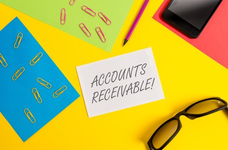 Photo for Text sign showing Accounts Receivable. Business photo text Legal Claim of Payment Money Owed to by Debtors Paper sheets pencil clips smartphone eyeglasses notebook color background - Royalty Free Image