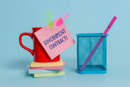 Handwriting text writing Government Contract. Conceptual photo Agreement Process to sell Services to the Administration Cup note arrow banners stacked pads metal pen holder pastel background