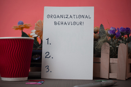 Photo pour Handwriting text writing Organizational Behaviour. Conceptual photo the study of the way showing interact within groups Flowers and stationary plus plain sheet with paper big cup above a table - image libre de droit