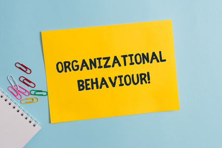 Photo pour Text sign showing Organizational Behaviour. Business photo showcasing the study of the way showing interact within groups Plain cardboard and writing equipment placed above pastel colour backdrop - image libre de droit
