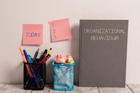 Photo pour Text sign showing Organizational Behaviour. Business photo showcasing the study of the way showing interact within groups Stick Pad Notes on Wall Two Pencil Pots Hardcover Notebook on Work Desk - image libre de droit