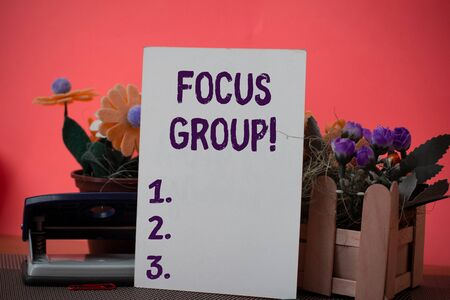Photo pour Text sign showing Focus Group. Business photo showcasing showing assembled to participate in discussion about product Flowers and writing equipments plus plain sheet above textured backdrop - image libre de droit