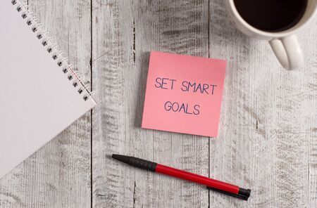 Foto de Handwriting text Set Smart Goals. Conceptual photo giving criteria to guide in the setting of objectives Stationary placed next to a cup of black coffee above the wooden table - Imagen libre de derechos