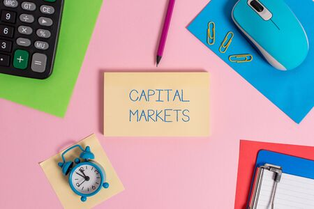 Conceptual hand writing showing Capital Markets. Concept meaning Allow businesses to raise funds by providing market security Mouse calculator sheets marker clipboard clock color background