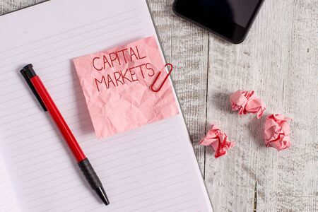 Writing note showing Capital Markets. Business concept for Allow businesses to raise funds by providing market security Wrinkle paper notebook and stationary placed on wooden background