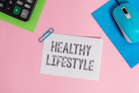 Conceptual hand writing showing Healthy Lifestyle. Concept meaning Live Healthy Engage in physical activity and exercise Wire electronic mouse calculator paper colored background