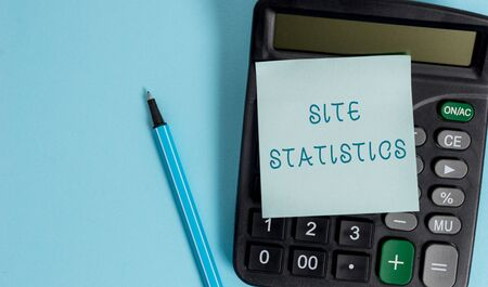Conceptual hand writing showing Site Statistics. Concept meaning measurement of behavior of visitors to certain website Electronic calculator sticky note marker colored background