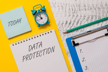 Foto de Conceptual hand writing showing Data Protection. Concept meaning Protect IP addresses and demonstratingal data from harmful software Spiral notepad sheet marker alarm clock wooden background - Imagen libre de derechos