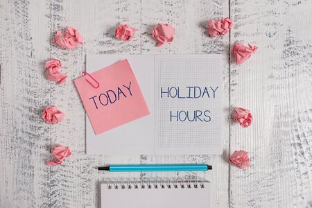 Text sign showing Holiday Hours. Business photo text employee receives twice their normal pay for all hours Squared spiral notepad clip note highlighter paper balls wooden background