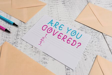Foto de Word writing text Are You Covered Question. Business photo showcasing asking showing if they had insurance in work or life Envelopes highlighters ruled paper sheet wooden retro vintage background - Imagen libre de derechos