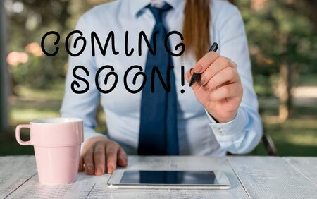 Writing note showing Coming Soon. Business concept for event or action that will happen after really short time Female business person sitting by table and holding mobile phone
