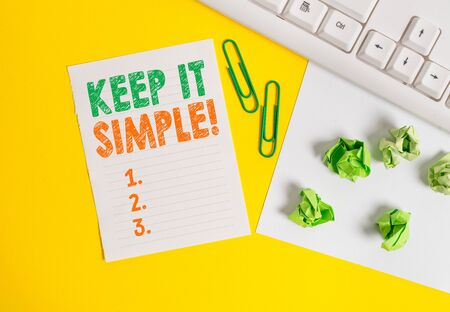 Photo pour Conceptual hand writing showing Keep It Simple. Concept meaning ask something easy understand not go into too much detail Flat lay with copy space white paper with paper clips on the table - image libre de droit