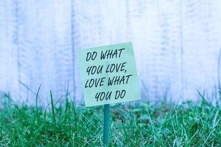 Photo for Word writing text Do What You Love Love What You Do. Business photo showcasing Pursue your dreams or passions in life Plain empty paper attached to a stick and placed in the green grassy land - Royalty Free Image