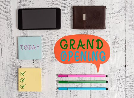 Foto de Word writing text Grand Opening. Business photo showcasing Ribbon Cutting New Business First Official Day Launching Smartphone pens blank speech bubble sticky notes wallet wooden background - Imagen libre de derechos