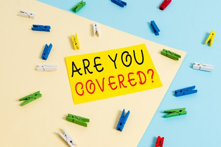 Foto de Text sign showing Are You Covered Question. Business photo text asking showing if they had insurance in work or life Colored clothespin paper empty reminder yellow blue floor background office - Imagen libre de derechos