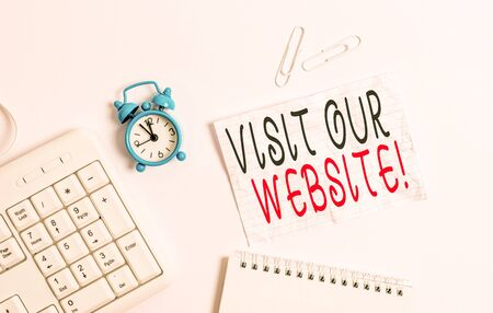 Photo pour Writing note showing Visit Our Website. Business concept for visitor who arrives at web site and proceeds to browse Blank paper with copy space on the table with clock and pc keyboard - image libre de droit