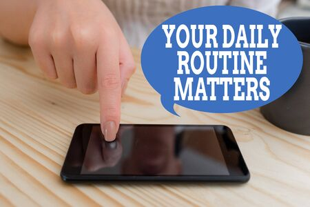 Photo pour Text sign showing Your Daily Routine Matters. Business photo text practice of regularly doing things in fixed order woman using smartphone office supplies technological devices inside home - image libre de droit