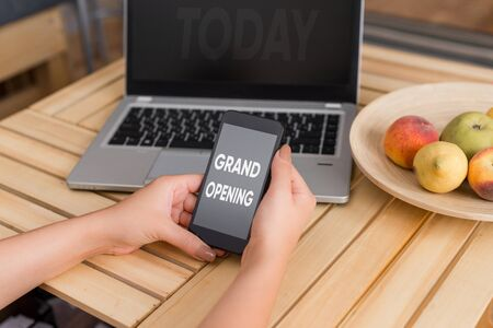 Foto de Conceptual hand writing showing Grand Opening. Concept meaning Ribbon Cutting New Business First Official Day Launching woman with laptop smartphone and office supplies technology - Imagen libre de derechos