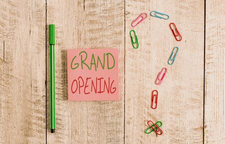 Foto de Word writing text Grand Opening. Business photo showcasing Ribbon Cutting New Business First Official Day Launching Pastel colour note paper placed next to stationary above the wooden table - Imagen libre de derechos