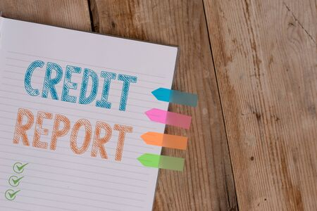 Photo for Handwriting text writing Credit Report. Conceptual photo Borrowing Rap Sheet Bill and Dues Payment Score Debt History Striped note book four colored arrow banners reminder wooden background - Royalty Free Image