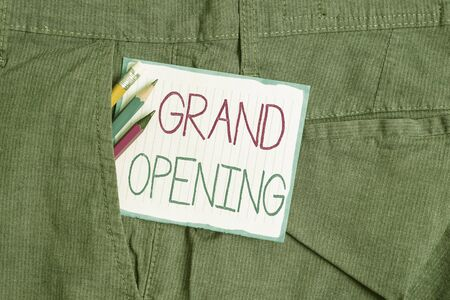 Foto de Handwriting text Grand Opening. Conceptual photo Ribbon Cutting New Business First Official Day Launching Writing equipment and white note paper inside pocket of man work trousers - Imagen libre de derechos