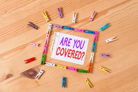 Foto de Handwriting text writing Are You Covered Question. Conceptual photo asking showing if they had insurance in work or life Colored clothespin papers empty reminder wooden floor background office - Imagen libre de derechos