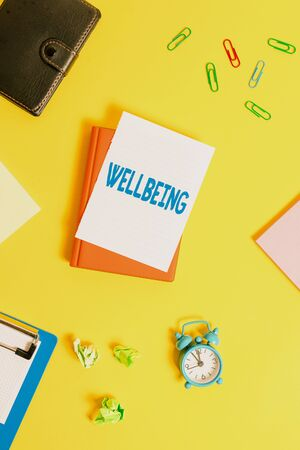 Photo pour Text sign showing Wellbeing. Business photo showcasing A good or satisfactory condition of existence including health Pile of empty papers with copy space on the table - image libre de droit