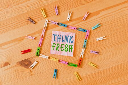 Photo pour Text sign showing Think Fresh. Business photo showcasing Thinking on natural ingredients Positive good environment Colored clothespin papers empty reminder wooden floor background office - image libre de droit