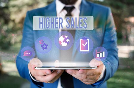 Foto de Word writing text Higher Sales. Business photo showcasing The average sold products and services of a company has grown Male human wear formal work suit presenting presentation using smart device - Imagen libre de derechos