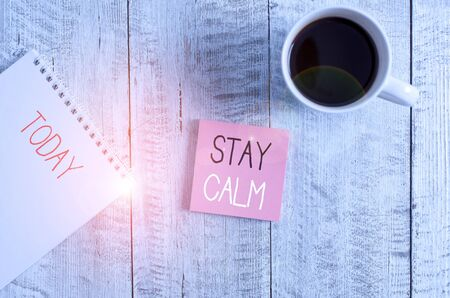 Foto de Conceptual hand writing showing Stay Calm. Concept meaning Maintain in a state of motion smoothly even under pressure Stationary placed next to a coffee cup above wooden table - Imagen libre de derechos