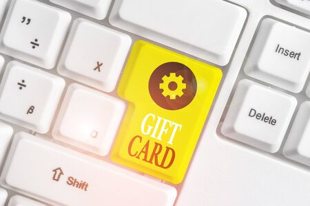 Conceptual hand writing showing Gift Card. Concept meaning A present usually made of paper that contains your message White pc keyboard with note paper above the white background