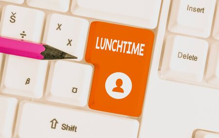 Conceptual hand writing showing Lunchtime. Concept meaning Meal in the middle of the day after breakfast and before dinner White pc keyboard with note paper above the white background