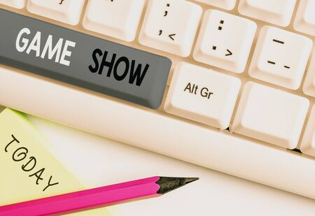 Writing note showing Game Show. Business concept for Program in television or radio with players that win prizes White pc keyboard with note paper above the white background