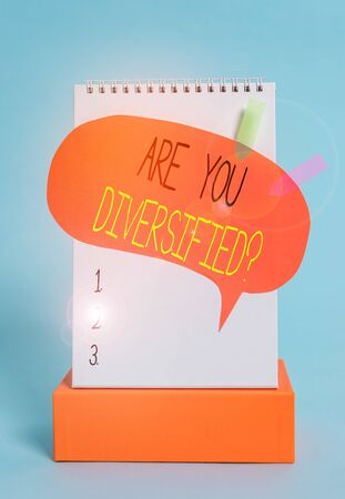 Writing note showing Are You Diversified Question. Business concept for someone who is Different Mixed Multi Faceted Spiral notepad box speech bubble arrow banners cool colored background