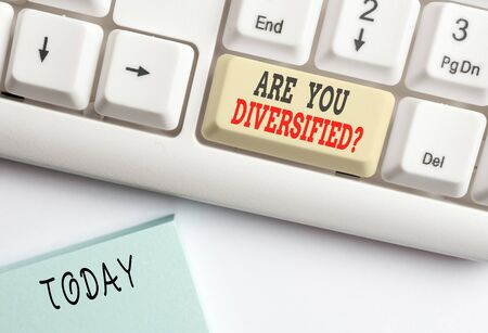 Conceptual hand writing showing Are You Diversified Question. Concept meaning someone who is Different Mixed Multi Faceted White pc keyboard with note paper above the white background