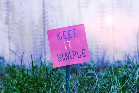 Photo pour Writing note showing Keep It Simple. Business concept for to make something easy to understand and not in fancy way Plain paper attached to stick and placed in the grassy land - image libre de droit