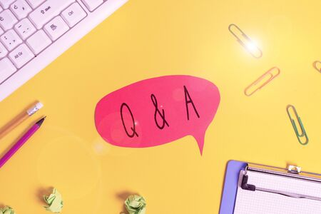 Foto de Conceptual hand writing showing Q And A. Concept meaning defined as questions being asked and answers Flat lay above empty paper with copy space and colored paper clips - Imagen libre de derechos