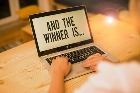 Photo pour Writing note showing And The Winner Is. Business concept for announcing a demonstrating or thing that wins something woman with laptop smartphone and office supplies technology - image libre de droit