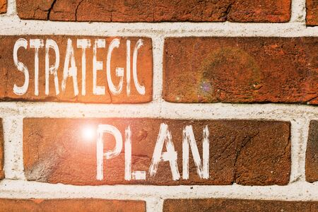 Photo pour Writing note showing Strategic Plan. Business concept for a systematic process of envisioning a desired future Front view red brick wall facade background Old grunge scenery - image libre de droit