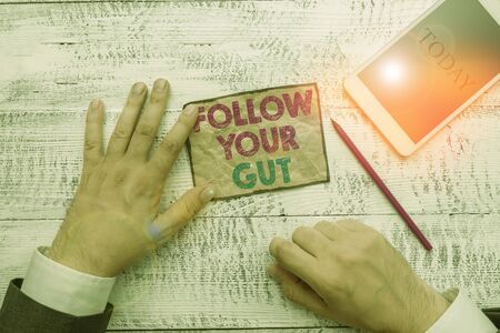 Photo pour Text sign showing Follow Your Gut. Business photo text Listen to intuition feelings emotions conscious perception Hand hold note paper near writing equipment and modern smartphone device - image libre de droit