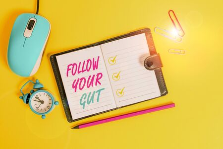 Photo pour Word writing text Follow Your Gut. Business photo showcasing Listen to intuition feelings emotions conscious perception Locked diary sheets clips marker mouse alarm clock colored background - image libre de droit