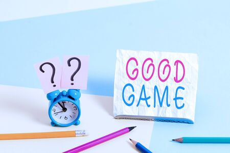 Writing note showing Good Game. Business concept for term frequently used in multiplayer gaming at the end of a match Mini size alarm clock beside stationary on pastel backdrop