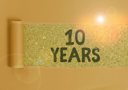 Foto de Text sign showing 10 Years. Business photo text Remembering or honoring special day for being 10 years in existence Cardboard which is torn in the middle placed above a wooden classic table - Imagen libre de derechos