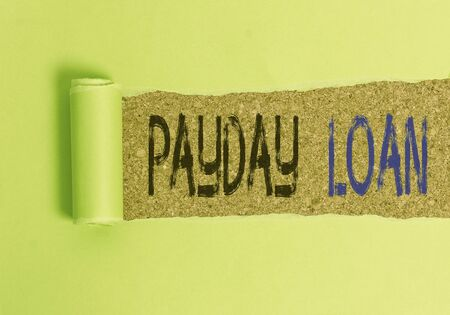 Photo for Text sign showing Payday Loan. Business photo text Something lent or furnished on condition being returned Cardboard which is torn in the middle placed above a wooden classic table - Royalty Free Image